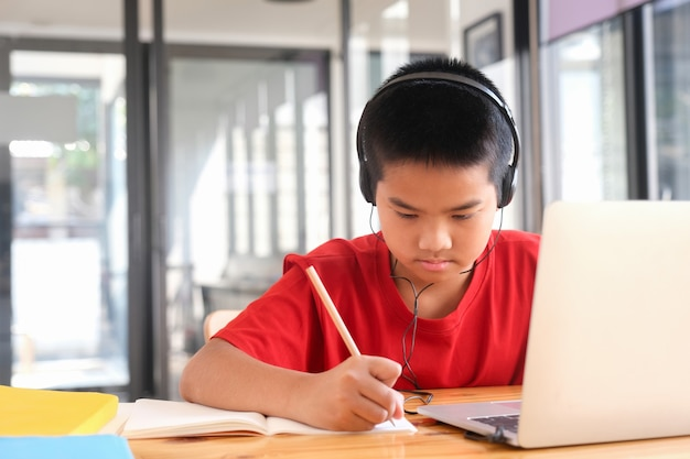 Jeune étudiant en collage utilisant un ordinateur et un appareil mobile étudiant en ligne. éducation et apprentissage en ligne.