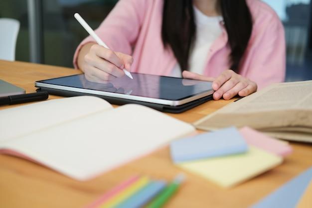 Jeune étudiant en collage utilisant un ordinateur et une tablette numérique étudiant en ligne.