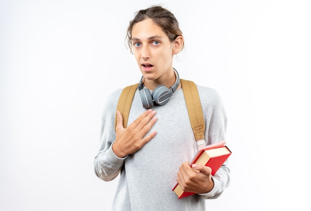 Jeune étudiant confus portant un sac à dos avec des écouteurs sur le cou tenant des livres mettant la main sur le coeur isolé sur un mur blanc