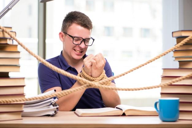 Jeune étudiant contraint d'étudier attaché