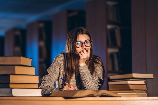 Jeune étudiant dans des verres se préparant à l'examen. fille le soir est assise à une table dans la bibliothèque avec une pile de livres