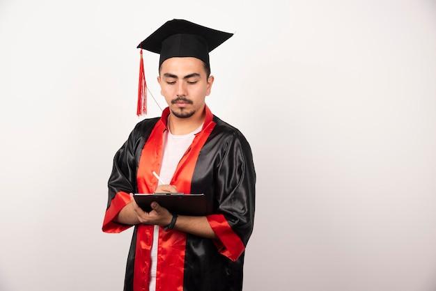 Jeune étudiant diplômé écrit sur blanc.