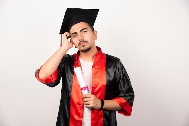 Jeune étudiant avec diplôme pensant sur blanc.