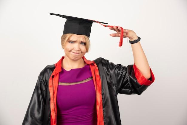 Jeune étudiant diplômé en robe regardant la caméra sur blanc.