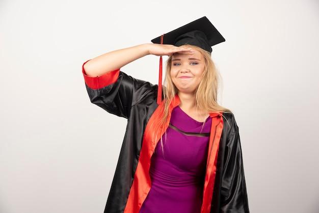 Jeune étudiant diplômé en robe se sentant heureux sur blanc.