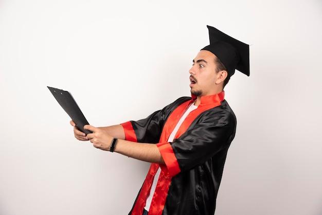 Jeune étudiant diplômé son diplôme sur blanc.