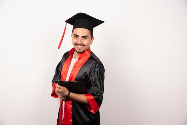Jeune étudiant diplômé en uniforme détenant un diplôme sur blanc.