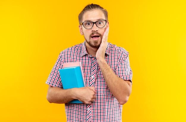 Jeune étudiant effrayé portant un sac à dos avec des lunettes tenant un livre mettant la main sur la joue
