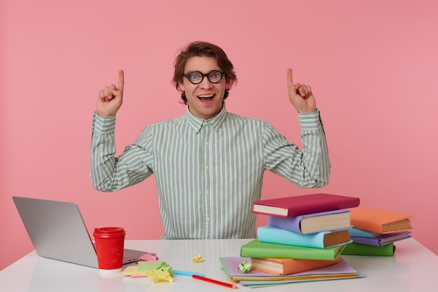 Jeune étudiant étonné heureux dans des verres, s'assoit près de la table et travaille avec un ordinateur portable, regarde la caméra et veut vous attirer l'attention sur copispee au-dessus de sa tête, isolé sur fond rose.