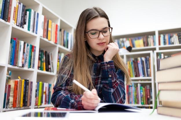 Jeune étudiant étudiant à la bibliothèque du campus