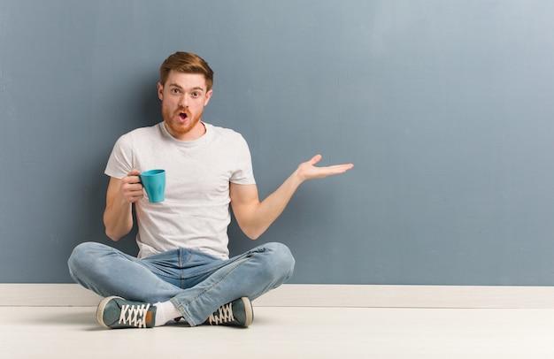 Jeune étudiant étudiant rousse assis sur le sol tenant quelque chose sur la main de la paume