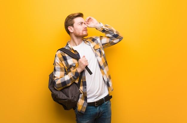 Jeune étudiant étudiant rousse faisant le geste d'une longue-vue