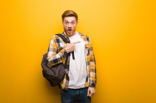Jeune étudiant étudiant rousse pointant sur le côté