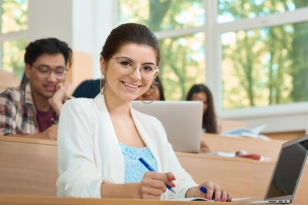 Jeune étudiant étudiant à l'université en regardant la caméra.