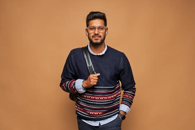 Jeune étudiant hindou barbu avec sac à dos sur mur pastel.