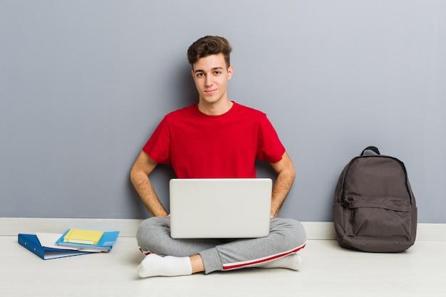Jeune étudiant homme assis sur le sol de sa maison tenant un ordinateur portable