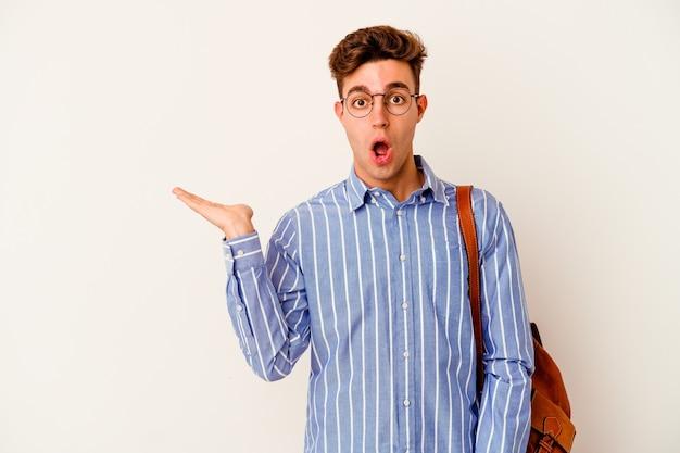 Jeune étudiant homme isolé sur un mur blanc impressionné tenant un espace de copie sur la paume