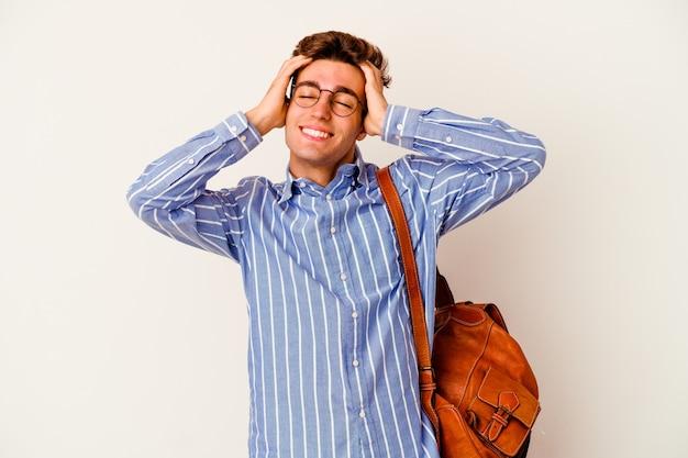 Jeune étudiant homme isolé sur un mur blanc rit joyeusement en gardant les mains sur la tête