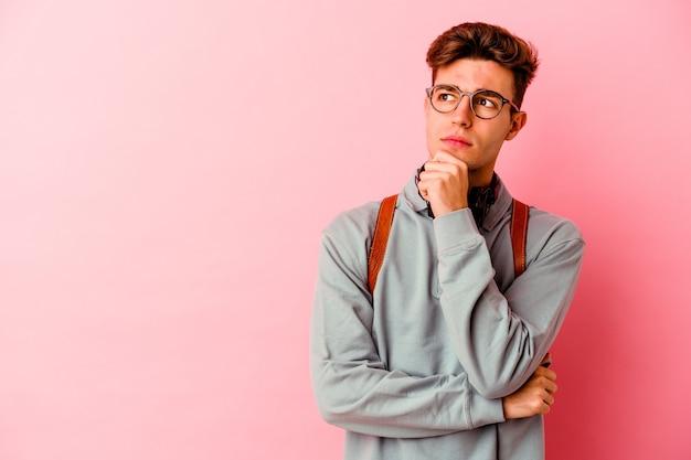 Jeune étudiant homme isolé sur un mur rose à la recherche de côté avec une expression douteuse et sceptique