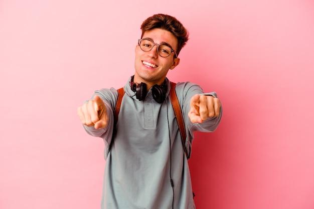 Jeune étudiant homme isolé sur mur rose sourires joyeux pointant vers l'avant
