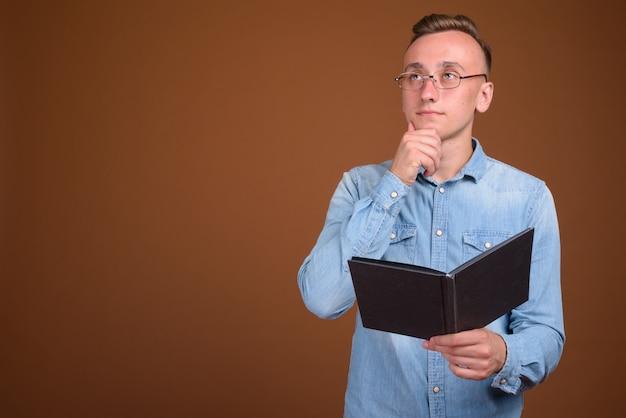 Jeune étudiant homme lisant un livre et pensant tout en levant