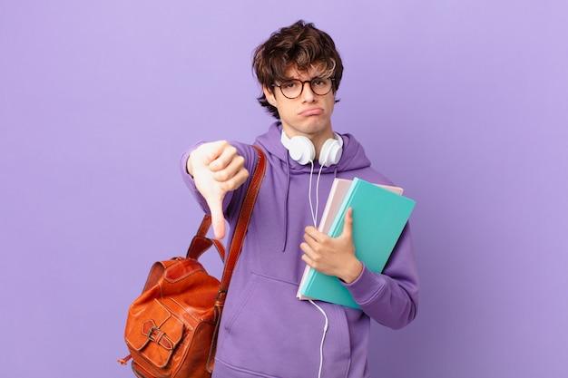 Jeune étudiant homme se sentant croisé, montrant les pouces vers le bas