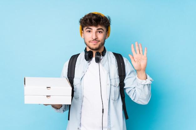Jeune étudiant homme tenant des pizzas souriant joyeux montrant le numéro cinq avec les doigts.