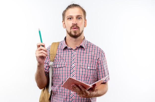 Jeune étudiant impressionné portant un sac à dos tenant un cahier avec un stylo isolé sur un mur blanc