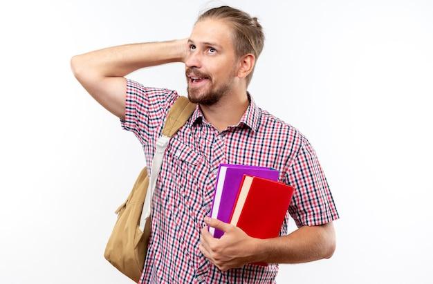 Jeune étudiant impressionné portant un sac à dos tenant des livres mettant la main sur la tête isolée sur un mur blanc