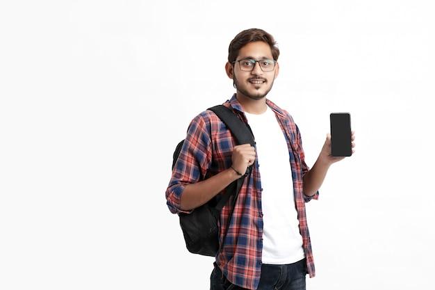 Jeune étudiant indien montrant l'écran du smartphone sur un mur blanc