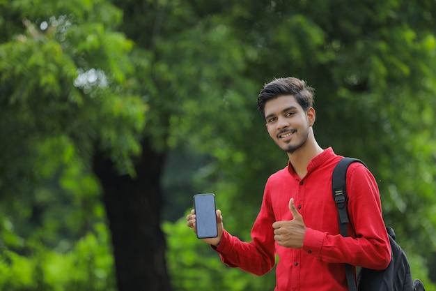 Jeune étudiant indien montrant un téléphone intelligent