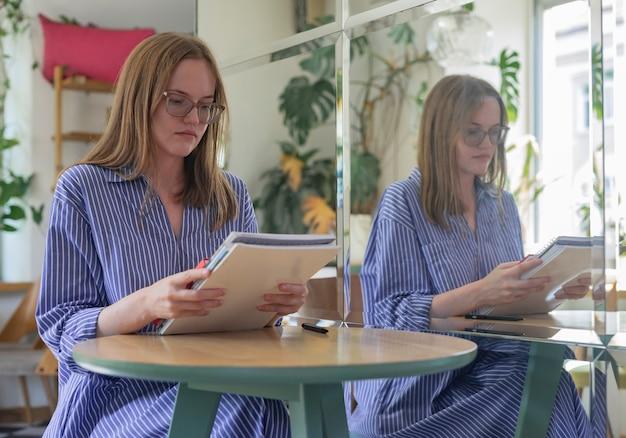 Jeune étudiant intelligent tenant des livres et des cahiers étudiant smth dans un café moderne avec miroir