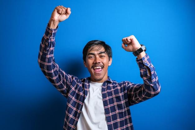 Jeune étudiant joyeux en vêtements décontractés isolé sur fond bleu studio leva le bras pour célébrer sa victoire