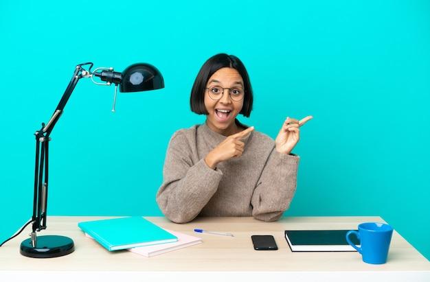 Jeune étudiant métisse femme étudiant sur une table effrayée et pointant vers le côté
