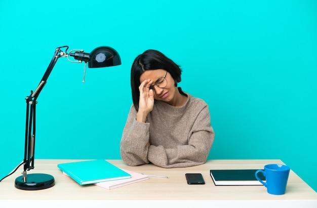 Jeune étudiant métisse femme étudiant sur une table avec une expression fatiguée et malade