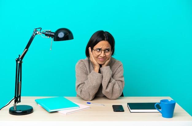 Jeune étudiant métisse femme étudiant sur une table frustré et couvrant les oreilles
