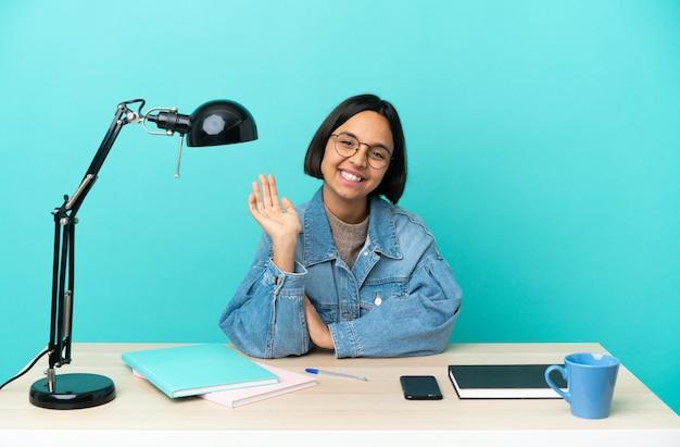 Jeune étudiant métisse femme étudiant sur une table saluant avec la main avec une expression heureuse