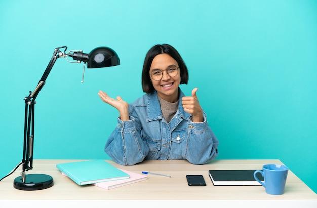 Jeune étudiant métisse femme étudiant sur une table tenant copyspace imaginaire sur la paume pour insérer une annonce et avec les pouces vers le haut
