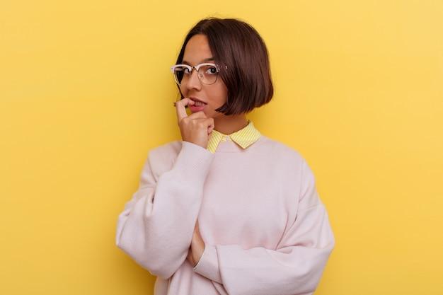 Jeune étudiant métisse femme isolée sur fond jaune détendu penser à quelque chose en regardant un espace de copie.