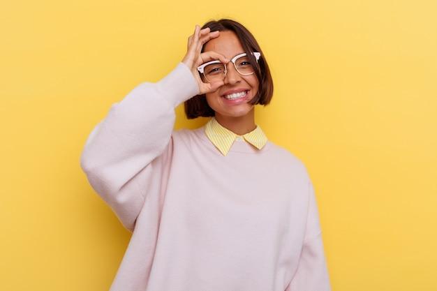 Jeune étudiant métisse femme isolée sur fond jaune excité en gardant le geste ok sur les yeux.