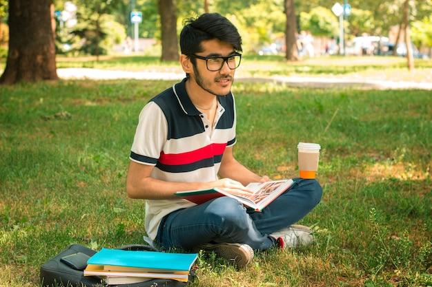 Jeune étudiant mignon assis sur une pelouse avec du café et des livres
