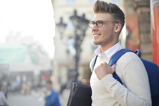 Jeune étudiant avec ordinateur portable et sac à dos