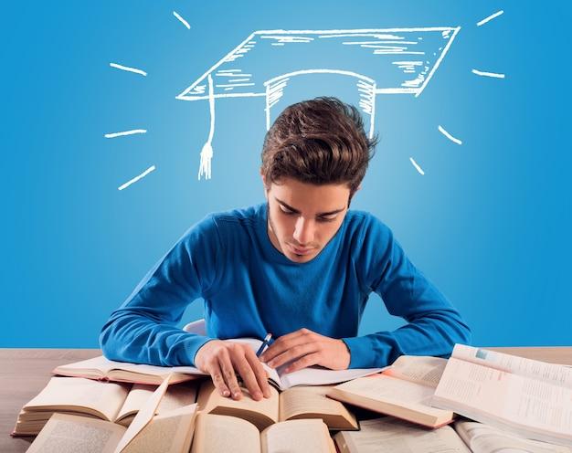 Jeune étudiant réfléchit à son diplôme pendant l'étude