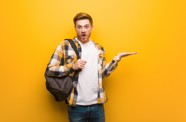 Jeune étudiant rousse homme tenant quelque chose sur la main de paume