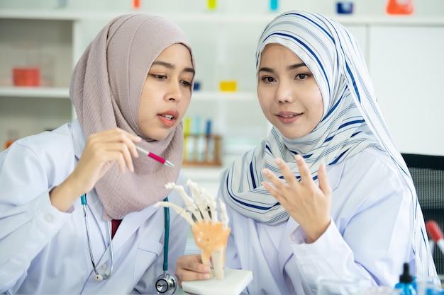 Jeune étudiant en sciences musulman asiatique faisant l'expérience en laboratoire dans leur université. des scientifiques musulmans enquêtant sur un échantillon chimique. développement de la technologie biologique dans le concept des pays asiatiques.