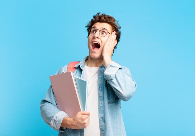 Jeune étudiant se sentant heureux, excité et surpris, regardant de côté avec les deux mains sur le visage