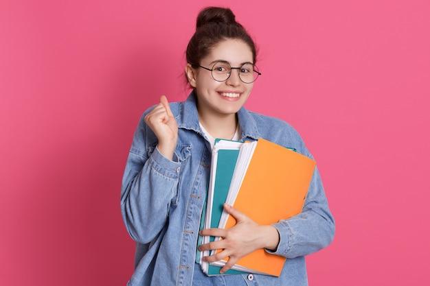 Jeune étudiant souriant à lunettes et veste en jean debout avec des dossiers en papier