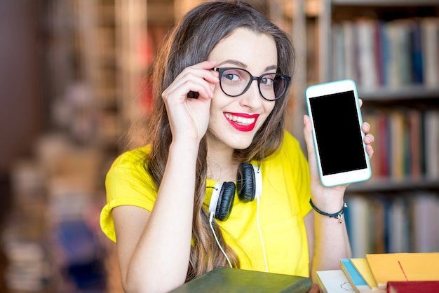 Jeune étudiant souriant montrant un téléphone intelligent avec un écran vide debout à la bibliothèque. concept d'applications mobiles