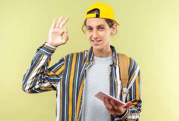 Jeune étudiant souriant portant un sac à dos avec une casquette tenant un ordinateur portable montrant un geste correct