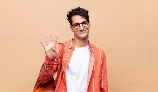 Jeune étudiant souriant et à la recherche amicale, montrant le numéro quatre ou quatrième avec la main en avant, compte à rebours
